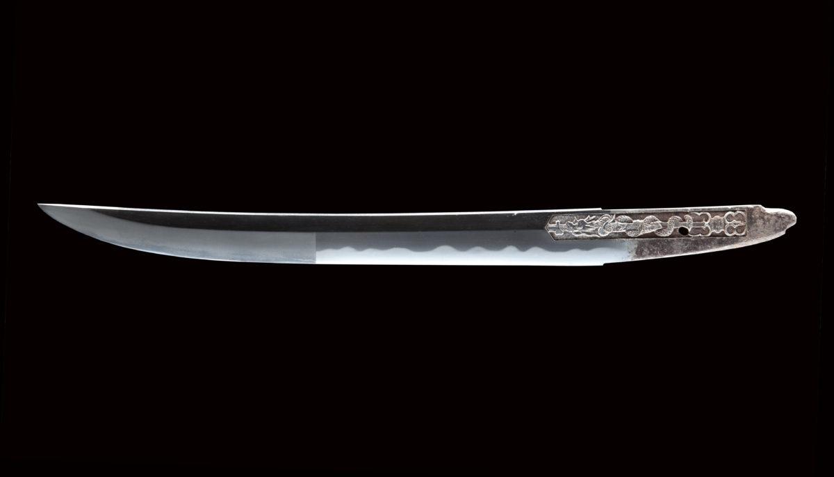薩州仁礼正真(文化1804年-1818年頃)は 薩州礼五郎も同名で伯耆守平朝臣正幸の門下。 ねむい刃を焼き、出来がどことなく師の伯耆守正幸に似ている。 本作、大磨上げで大切先(16.6cm)で身幅広く(34.2mm)あり、力強く強調され覇気ある一振り。 表に真ノ倶利迦羅、裏に不動明王を彫り、刀を超越した正に守り刀と言えよう。 鎬作り、庵棟、姿は身幅広く大磨上げで覇気がある。 地鉄美しく板目よく詰み地錵かかる。刃文は錵深く、互ノ目乱れ。 鋒は乱れ込みながら、鋒先にかけ掃掛風に地刃に盛んに沸づき沸崩風。 全体的に錵深く砂流し入る。